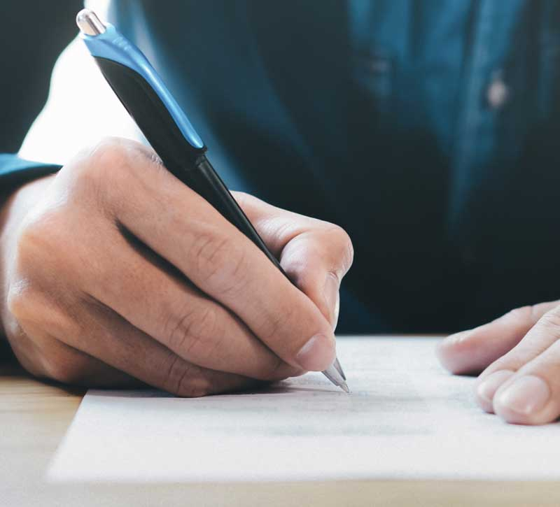 Photo of a hand signing paperwork.